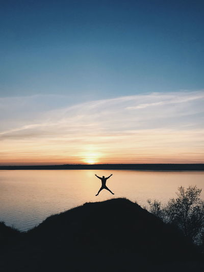 Silhouette person jumping against lake during sunset