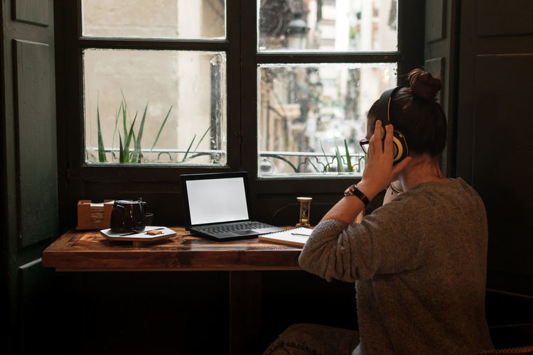 Rear view of woman using laptop on table