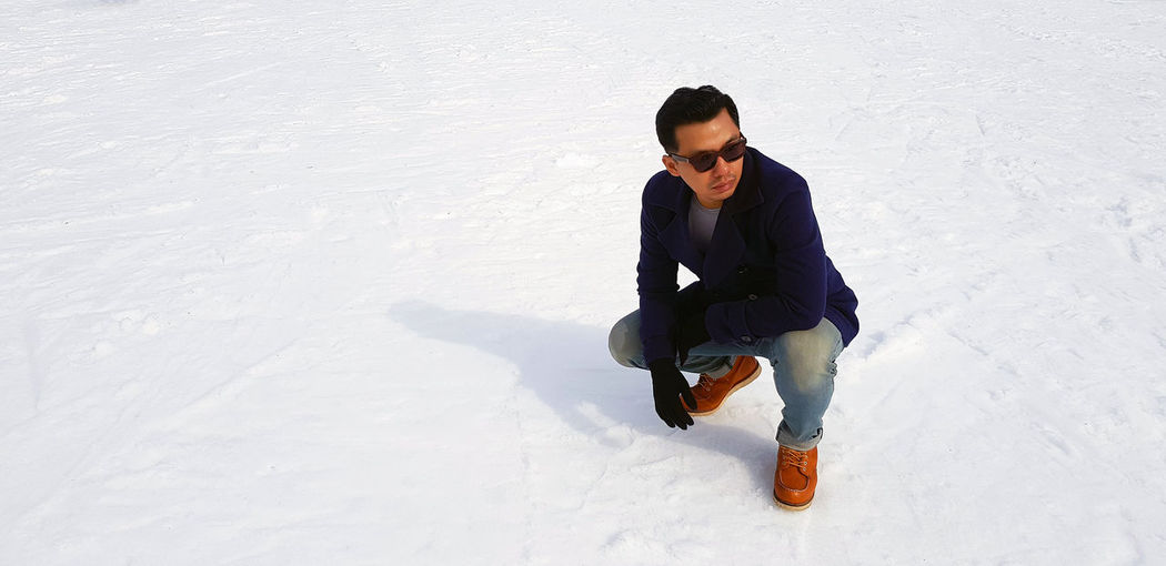 High angle view of young man in snow