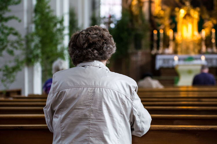 Rear View Of Woman Sitting On Bench In Heiliggeistkirche