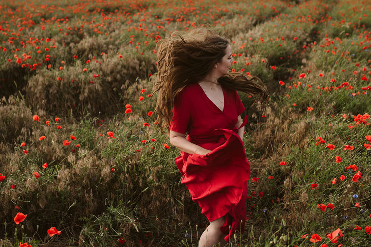 Rear view of woman with red flowers on field