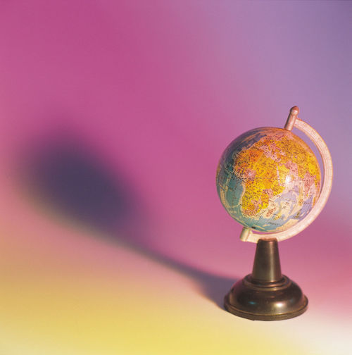 Close-up of globe against colored background
