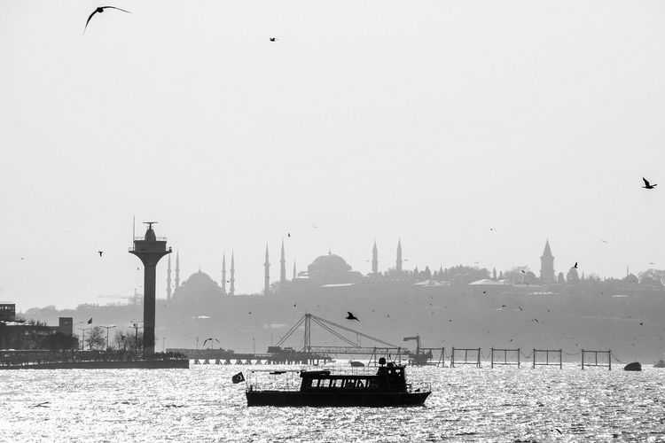 Silhouette boat sailing in straits by mosque against clear sky