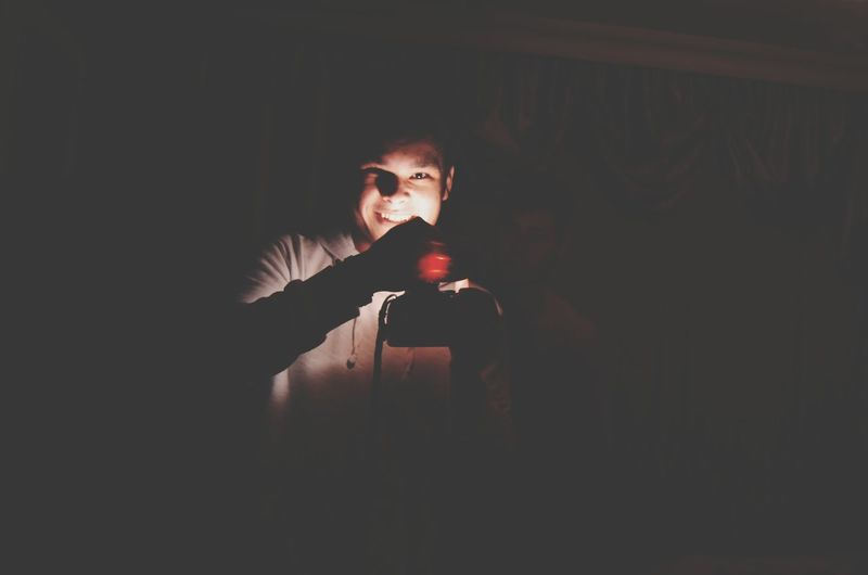 Portrait of young man standing in darkroom