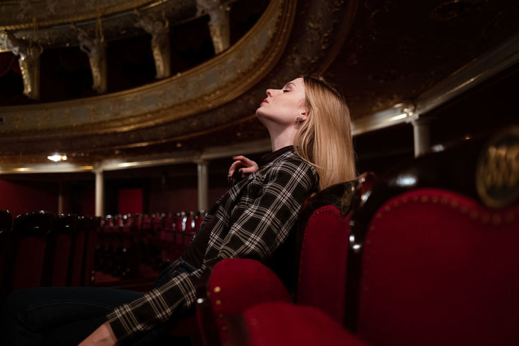 Woman looking down while sitting on seat at opera theatre with long blonde hair
