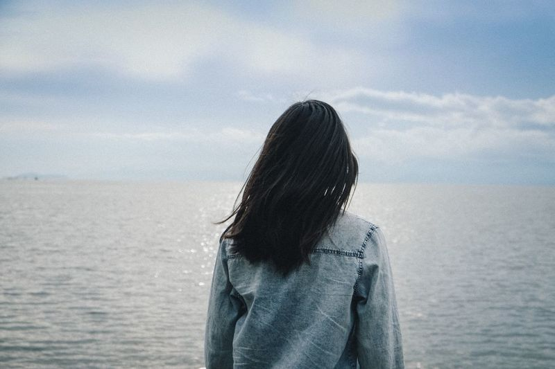 One Person Real People Lifestyles Waist Up Standing Casual Clothing Women Leisure Activity Sky Day Hairstyle Water Nature Hair Long Hair Rear View Outdoors Cloud - Sky Warm Clothing Obscured Face