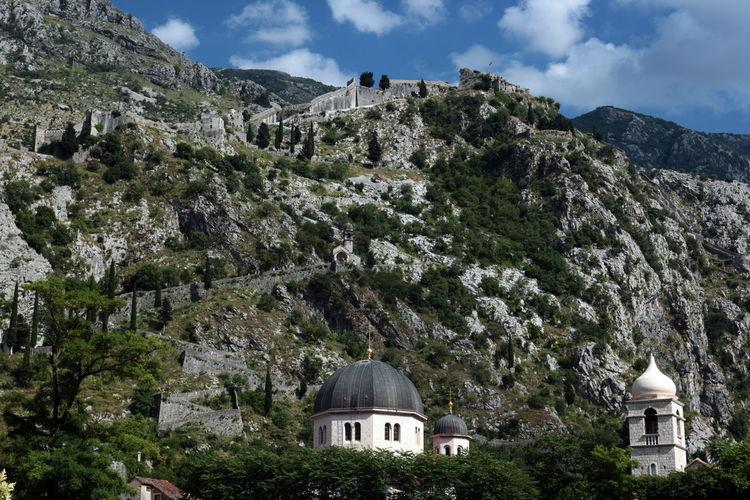 Church on mountain against cloudy sky