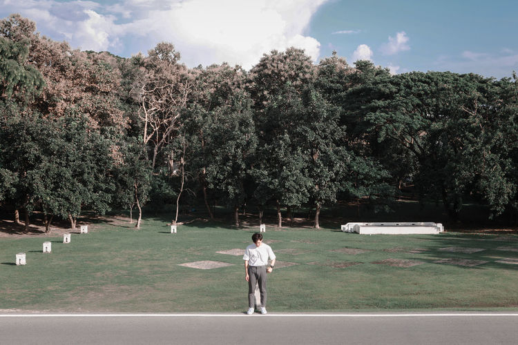 Rear view of man walking by trees against sky