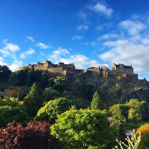 Low Angle View Of Edinburgh Castle And Trees Against Cloudy Blue Sky