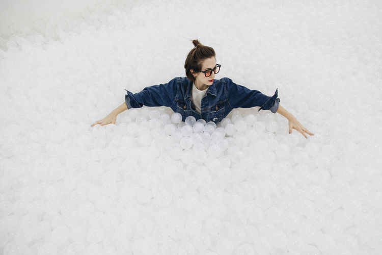High angle view of woman sitting amidst balls