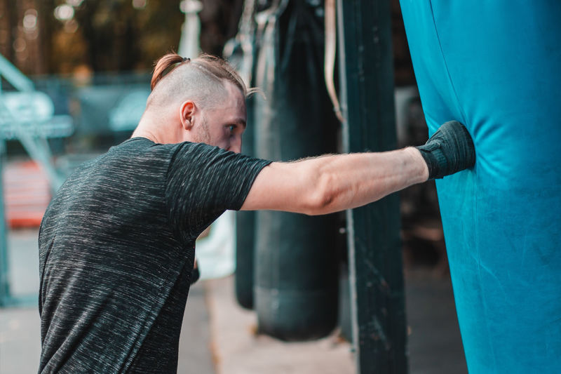 Side view of young man practicing boxing while standing outdoors