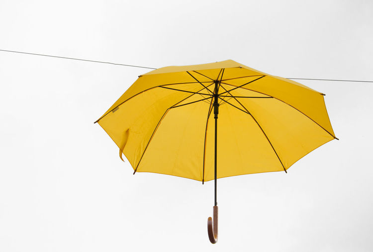 Close-up of yellow umbrella against white background