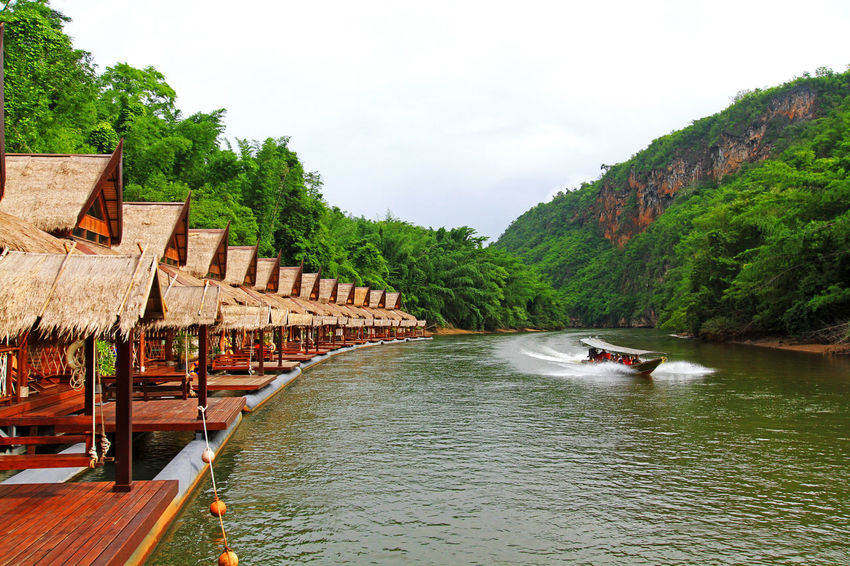 Many wooden house floating on the river with mountain and speed boat at Float house river kwai resort, Kanchanaburi, Thailand Beatiful Nature Relaxing Resort Hotel Thailand Vacations Architecture Beauty In Nature Boat Building Exterior Floating On Water Flotsam Forest House Jungle Landmark Landscape Mountain Nature Raft River Travel Destinations Tree Wooden House