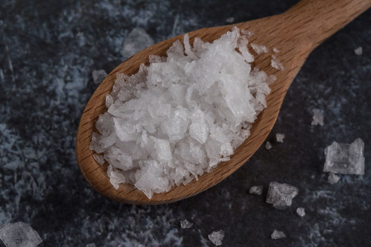 Close-Up Of Salt In Wooden Spoon On Table