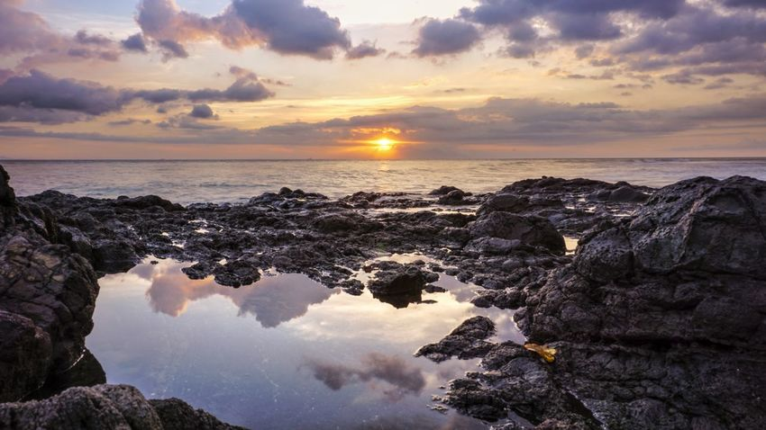 Sunset Cloud - Sky Sea Sky Reflection Water Sun Beach Horizon Over Water Outdoors Dusk Nature Sunlight No People Travel Destinations Scenics Vacations Landscape Beauty In Nature Tranquility