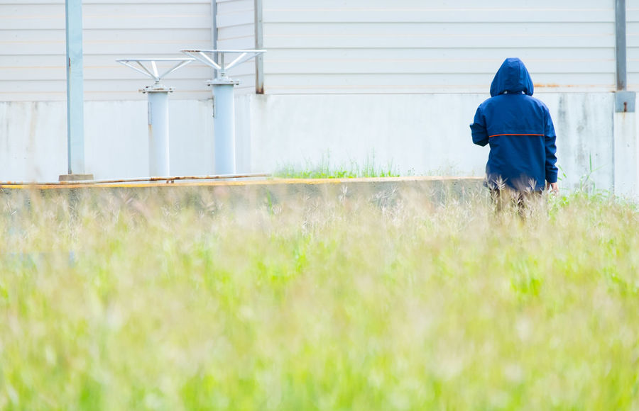 Rear View Real People Field Day One Person Land Nature Plant Hood Lifestyles Clothing Growth Outdoors Casual Clothing Hood - Clothing Grass Industry Factory Nature Field Standing Jacket Pink Color Worker Life