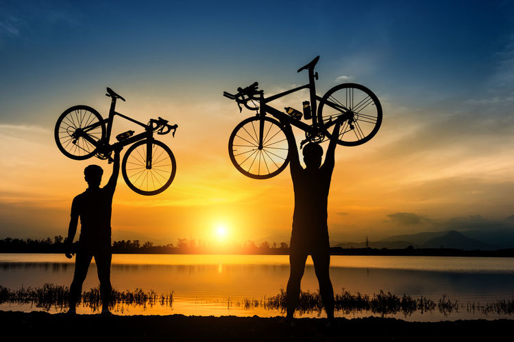 Silhouette two man stand in action lifting bicycle above his head near the river with sunset Friends Action Activity Adventure Bicycle Cloud - Sky Cycling Day Excercise Lake Leisure Activity Lifestyles Men Nature Orange Color Outdoors People Reflection Relax Riding Silhouette Sky Sport Sunset Water