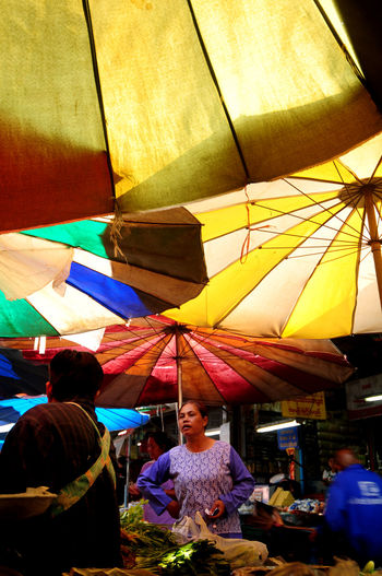 Market Colors Umbrella Colors Adult Awning Burmese Market Day Enjoyment Leisure Activity Lifestyles Market Market Umbrellas Men Multi Colored Outdoors People Real People Sitting Standing Tent Women