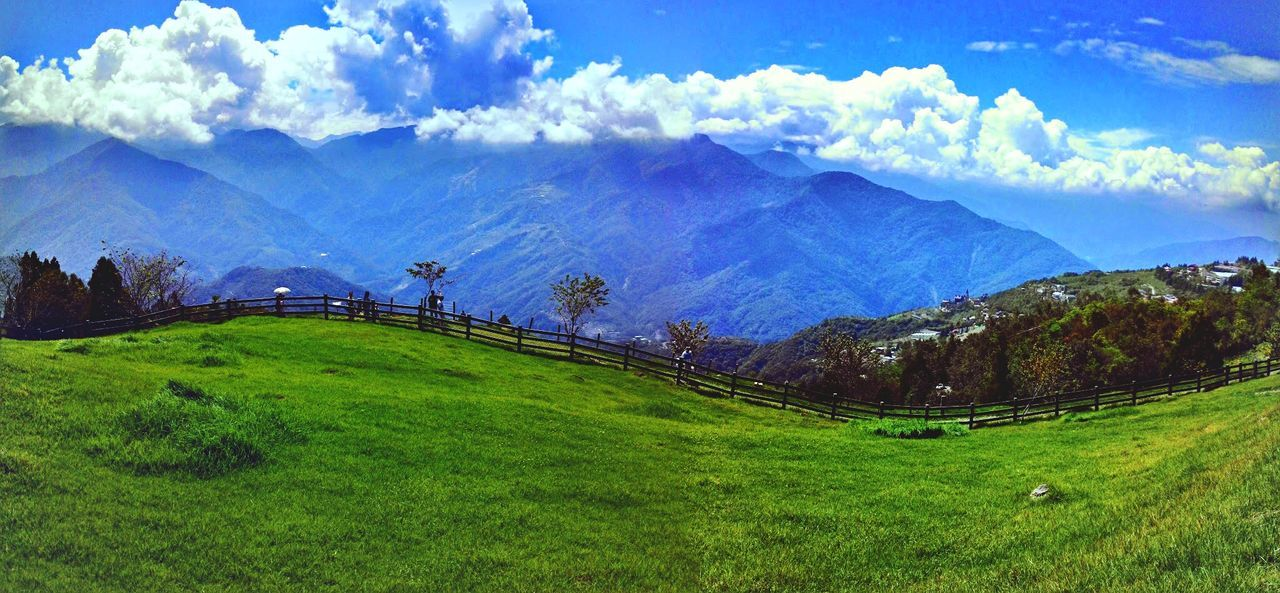 Scenic View Of Grassy Hill And Mountains Against Cloudy Blue Sky