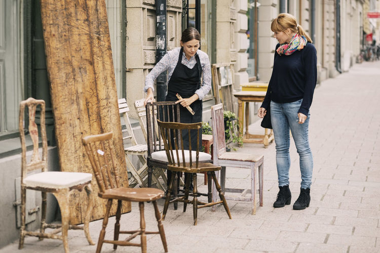 Women standing on chair at store