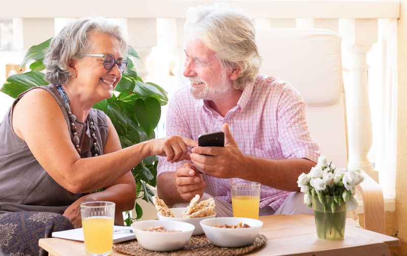 Senior man and woman using phone while sitting with breakfast at table