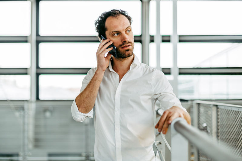 caucasian man talking on the phone Using Phone Telephone One Person Mobile Phone Technology Standing Communication Waist Up Front View Wireless Technology Males  Indoors  Holding Talking Looking Men Real People Adult Mature Adult Portable Information Device Mature Men Man Caucasian