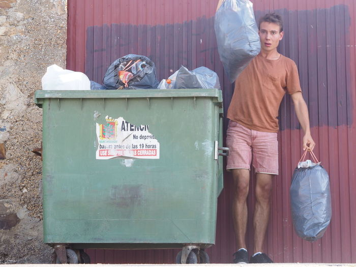 Full length portrait of young man holding garbage while standing by bin