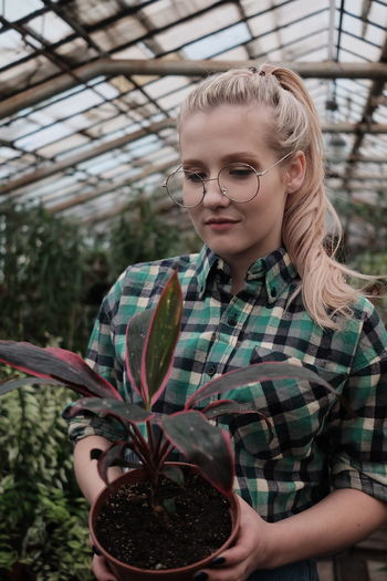 Young female caucasian gardener holding a house plant