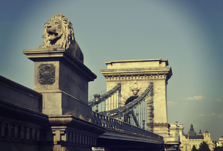 Low Angle View Of Lion Statue At Chain Bridge Against Sky