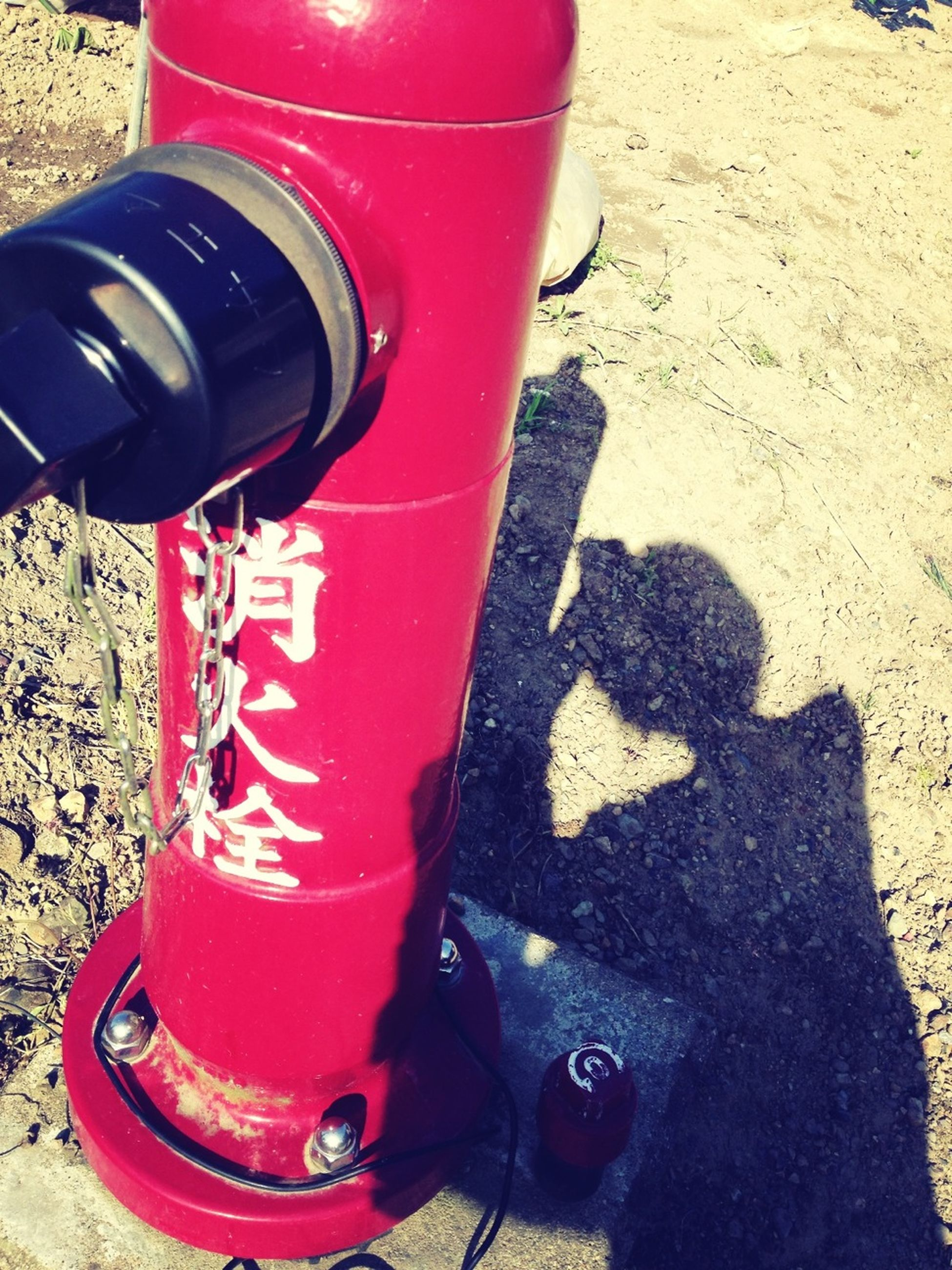 red, high angle view, shoe, close-up, sunlight, still life, sand, street, outdoors, shadow, land vehicle, low section, day, transportation, car, no people, single object, footwear, beach, bottle