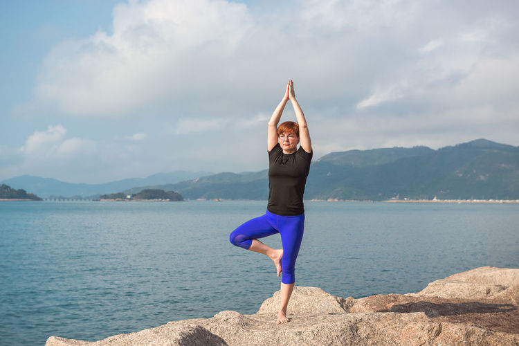 Exercising One Person Healthy Lifestyle Lifestyles Water Sky Full Length Wellbeing Mountain Leisure Activity Cloud - Sky Balance Beauty In Nature Human Arm Nature Sport Real People Yoga Tranquility Arms Raised Leg Outdoors Seashore Woman Adult