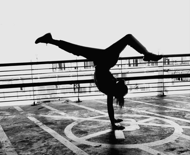 Full Length Side View Of Teenager Doing Handstand By Railing