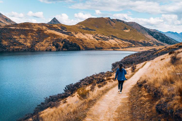 Rear view of man walking on lake against mountains