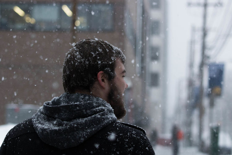 Rear view of young man in city during snowfall