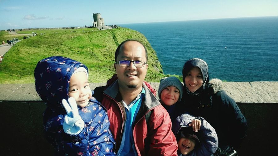 Happy family at Cliff of Moher, Ireland. Togetherness Looking At Camera Smiling Childhood Happiness Vacations Leisure Activity Standing Father Family Vacation Enjoyment EyeEmNewHere Childhood Fun Real People Autumn In Ireland Childhood Joy Sibling Bond Front View Close-up Warm Clothing Childhood Innocence Preschool Age Girl Wearing Cap Happy Girls Are The Prettiest  Toddler Girl Be. Ready.
