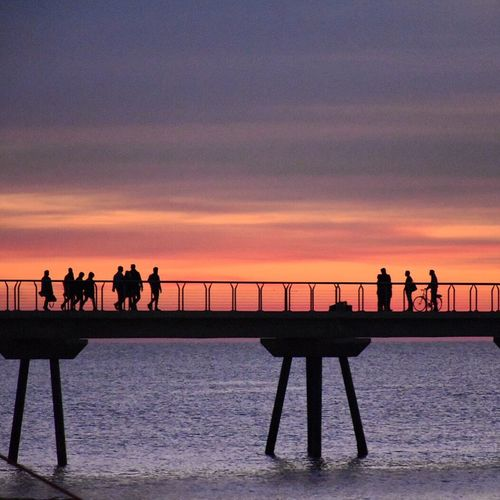 Silhouette people standing by railing during sunset