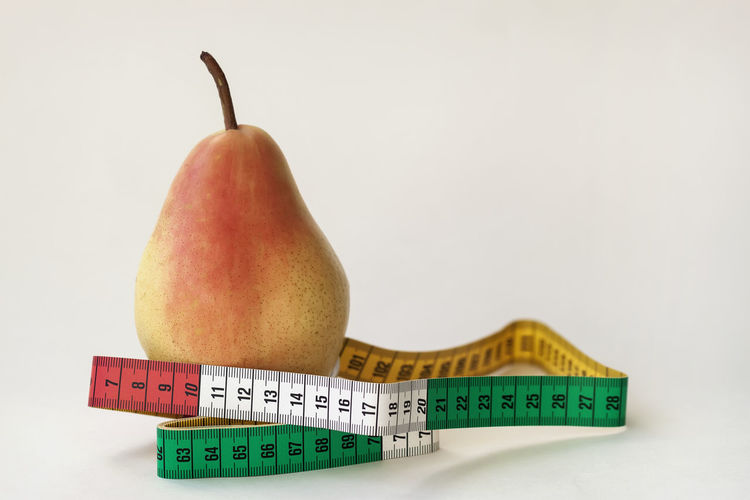 One ripe pear and colorful tape measure on light background, concept of a healthy lifestyle, diet, control of overweight Healthy Eating Fruit Food And Drink Food Still Life Wellbeing Freshness Close-up No People Pear Tape Measure Ripe Copy Space Dieting Healthy Lifestyle Healthy Healthy Food Bright Weight Figure Centimeter Energy Shape Calories Eat
