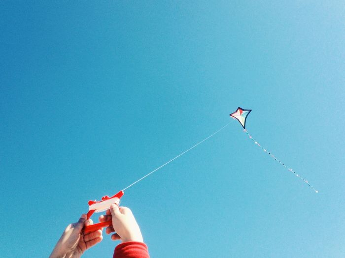 Close-up of hands flying kite against clear blue sky