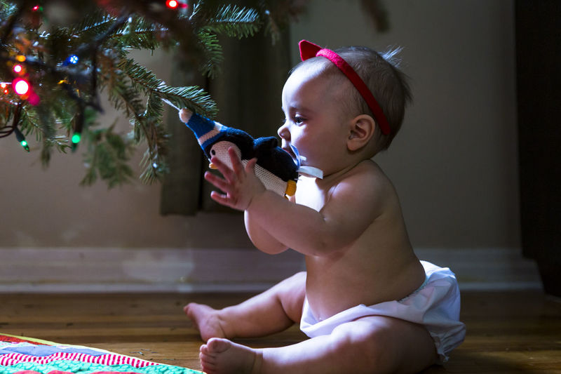 Naughty cute girl baby with red ribbon in her hair pulling christmas ornament from tree