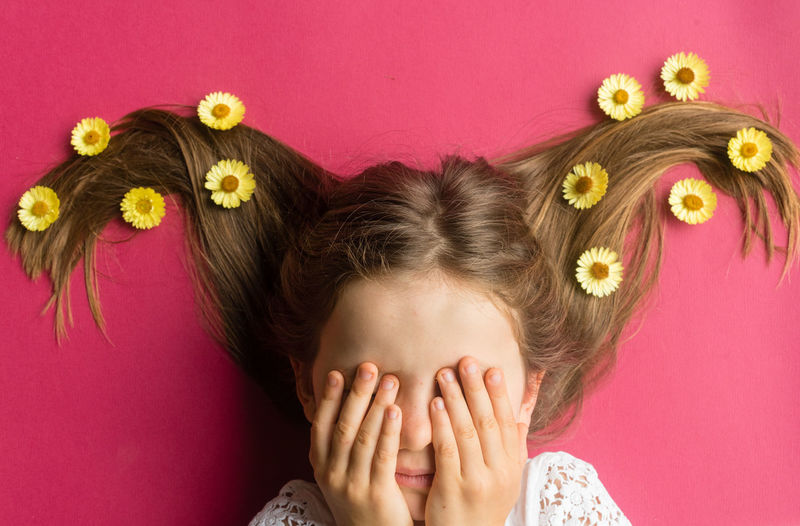 Directly above shot of girl with flowers on hair hiding face with hands over pink background