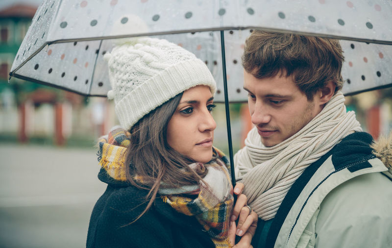 Portrait of young beautiful couple in love looking under the umbrella in an autumn rainy day. Love and couple relationships concept. Woman Cold Winter Hat Scarf Horizontal Rain Girl Young Female Outdoors Fall Real People Caucasian Two People Couple Love Realtionship Man Male Umbrella Rainy Happy Embracing Hugging