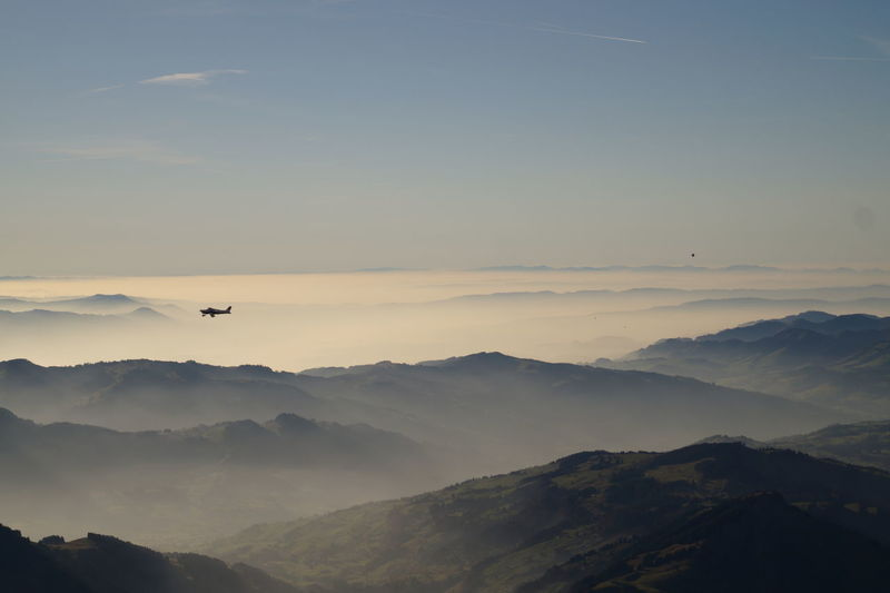 Scenic view of airplane flying over mountains against sky