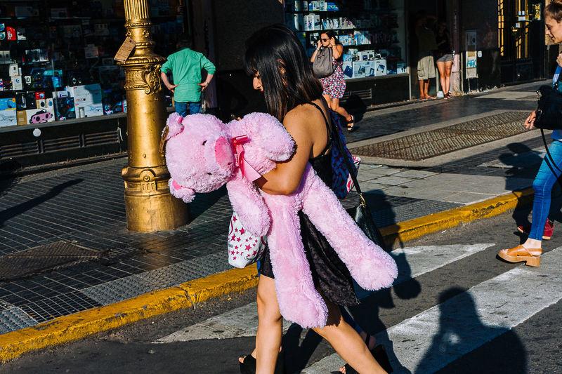 Rear view of women walking on road in city