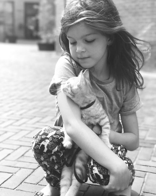Childhood One Person Real People Outdoors Focus On Foreground Girls Day Looking Down Casual Clothing Sitting Full Length Playing Leisure Activity Elementary Age Lifestyles Happiness Smiling Child Close-up People Girl Cat 愛アムステルダム 阿姆斯特丹