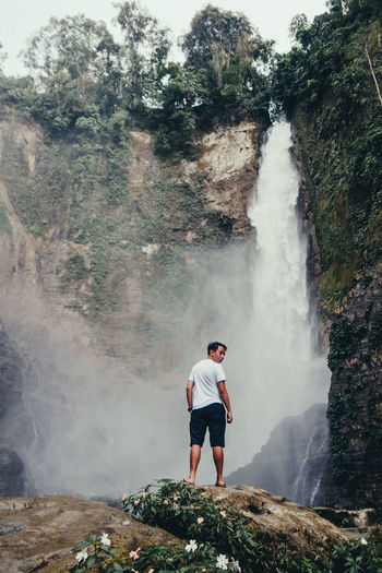Man surfing on waterfall in forest