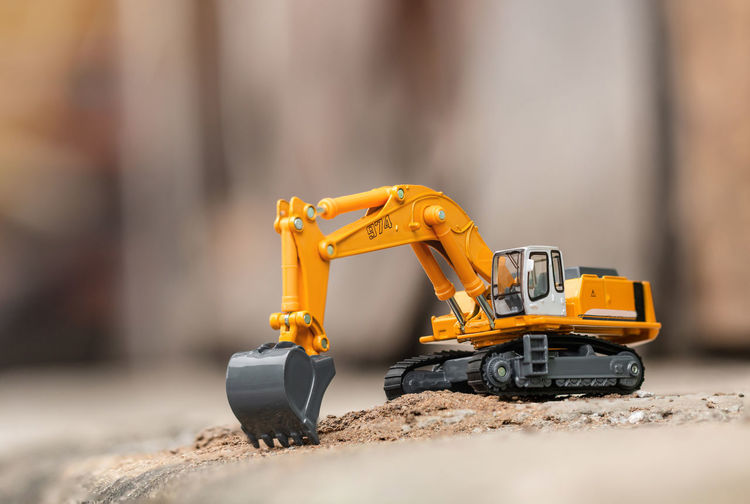 Yellow excavator model toy performs excavation work on a construction site. (Image stacking technique) Bulldozer Earth Mover Yellow Machinery Toy Model Land Excavator Excavation Construction Working Backhoe Digger Heavy Ground Loader Shovel Soil Sand Industry Dirt Bucket Building Crane - Construction Machinery Caterpillar