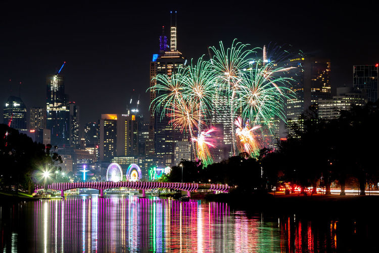 Firework display over river and illuminated buildings in city at night