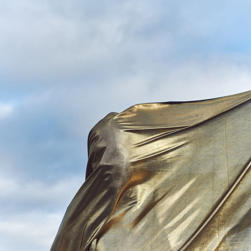 Man covered with fabric against sky