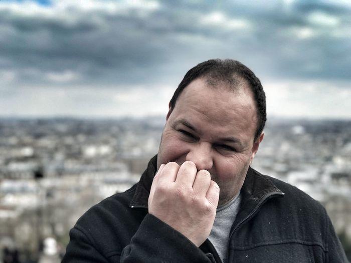 Close-up portrait of man biting fingernails standing against cityscape