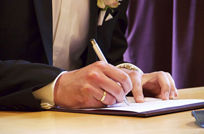 Midsection of bridegroom signing document on table during wedding